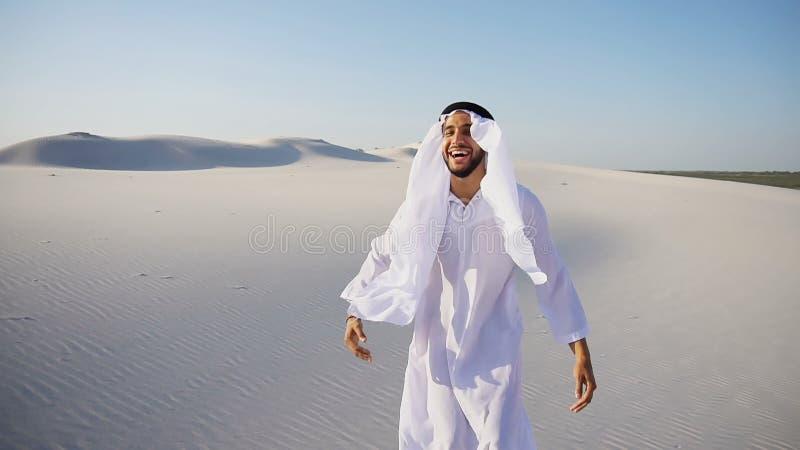 回教阿拉伯阿拉伯联合酋长国回教族长建筑师与膝上型计算机坐沙子 库存图片