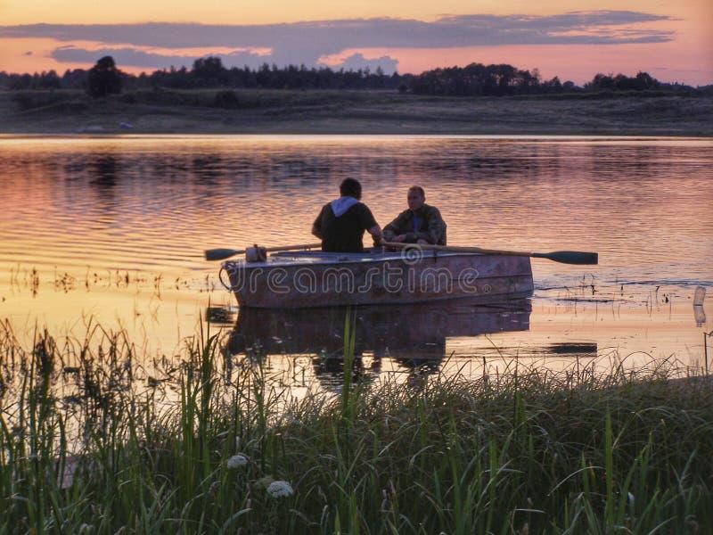 回来在日落Volgo湖俄罗斯的渔夫 免版税图库摄影