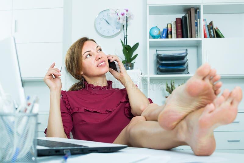 回答在电话和坐与腿的少妇雇员  免版税库存照片