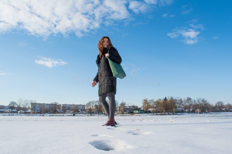 回顾一个年轻美丽的红色头发欧洲的女孩的画象走在多雪的结冰的河和 免版税库存照片