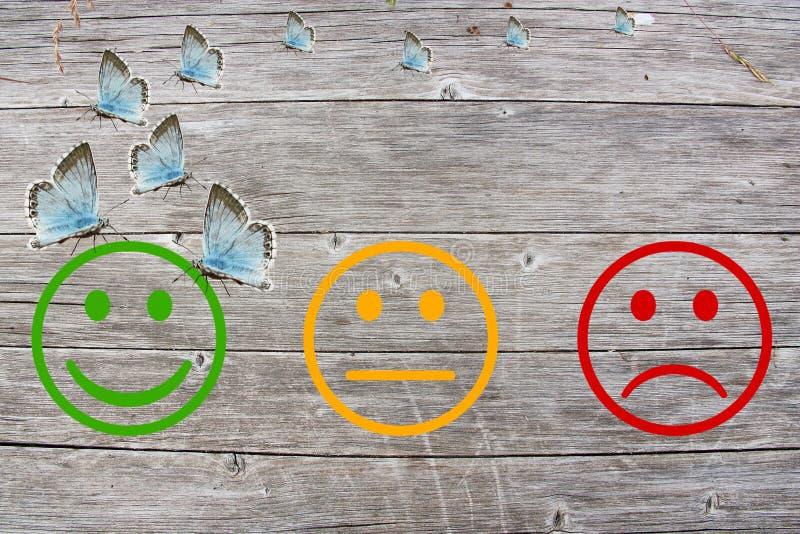 回顾与愉快和恼怒的面孔的分类在木背景 免版税图库摄影