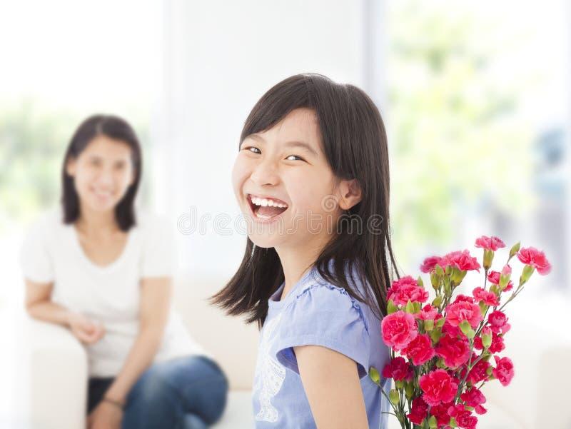 回顾和掩藏康乃馨的花束愉快的女孩 免版税图库摄影