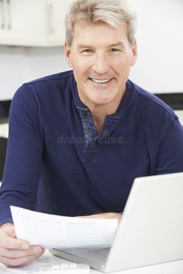 回顾国内财务的微笑的成熟人 免版税库存图片
