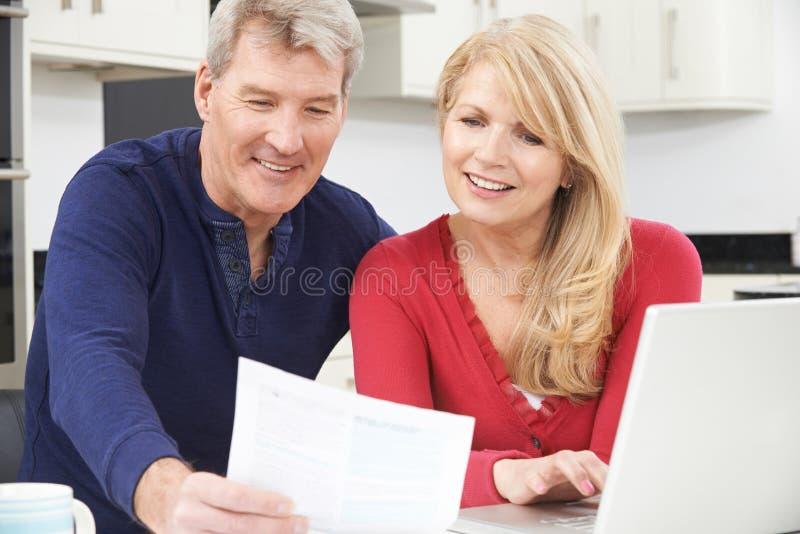 回顾国内财务的微笑的成熟夫妇 图库摄影