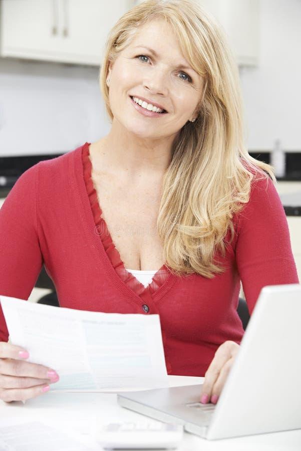 回顾国内财务的微笑的成熟妇女 免版税库存照片