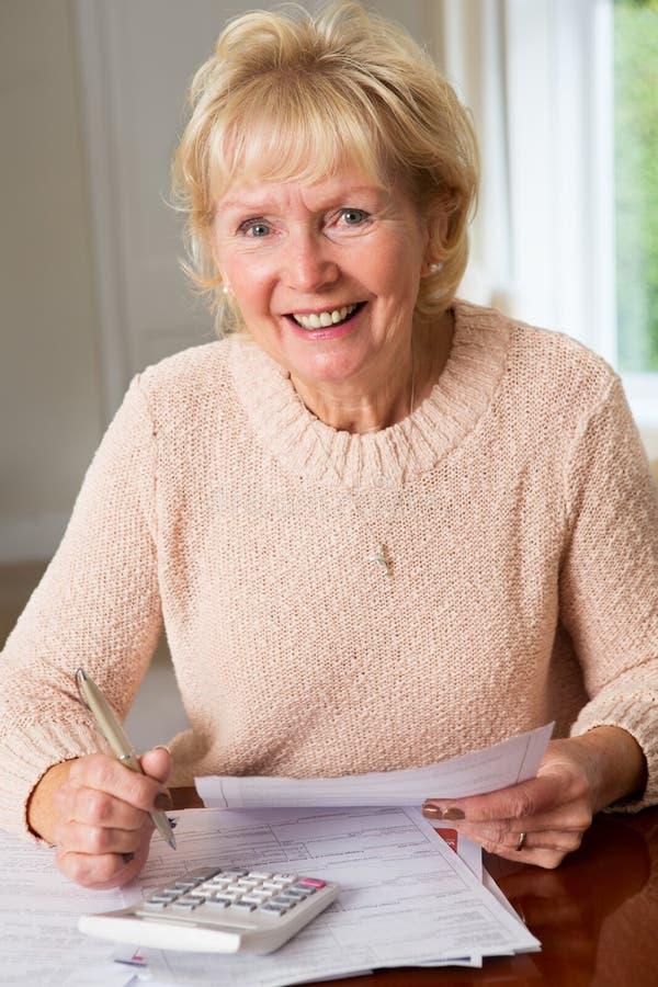 回顾国内财务的微笑的资深妇女 免版税图库摄影