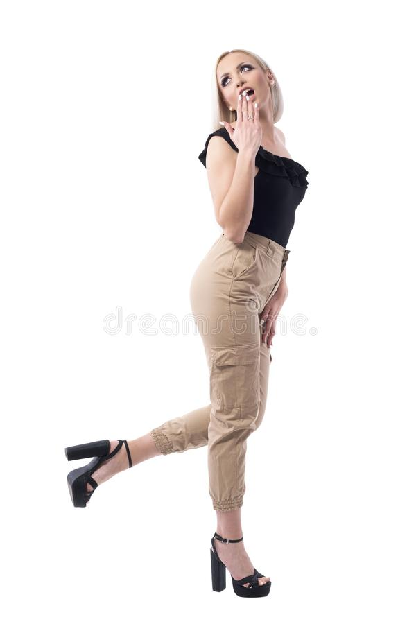 回顾在肩膀的惊奇的年轻女人侧视图  折扣概念 免版税库存图片