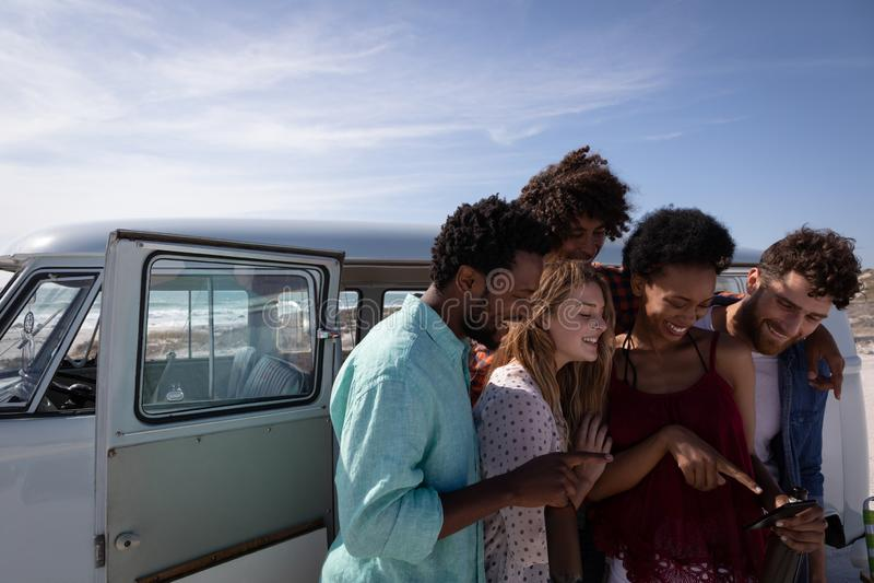 回顾照片的小组朋友在海滩 库存照片