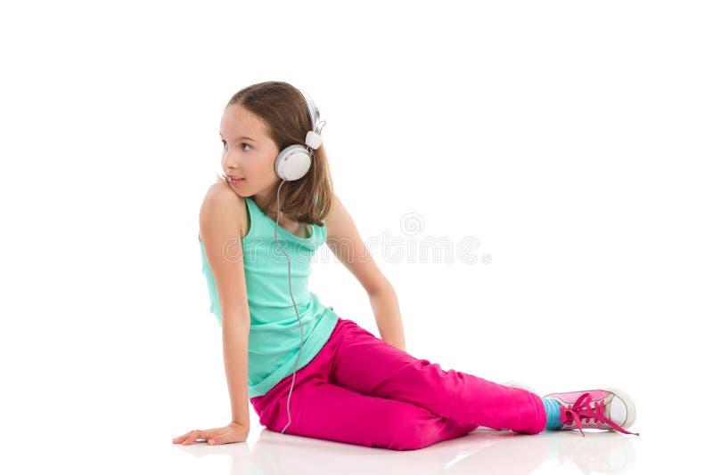 回顾的耳机的小女孩 免版税库存图片