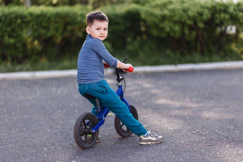 回顾的运动鞋的四岁的逗人喜爱的男孩 r 孩子和夏天 没有脚蹬的自行车 免版税库存图片
