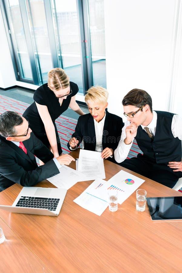 回顾财务数据文书工作的商人 免版税图库摄影