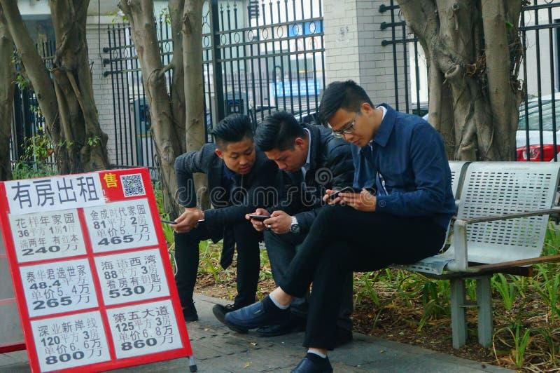 因为事务不是好,在街道的房地产开发商使用与一个手机 免版税图库摄影