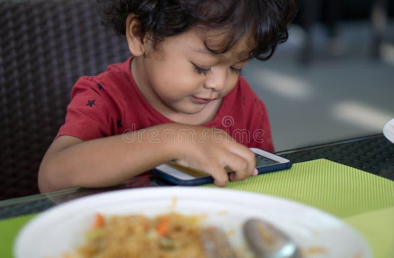 因为他们演奏智能手机,男孩不吃食物 图库摄影