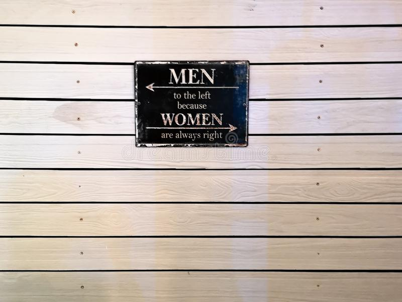 因为妇女总是正确,引述在木墙壁上的框架-人到左边 免版税库存图片