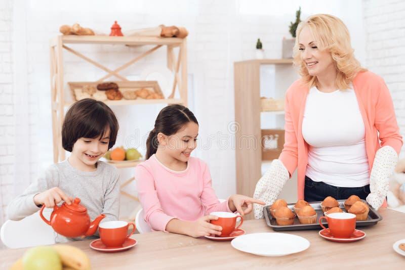 因为祖母烘烤了杯形蛋糕,愉快的孙女和孙子是乐趣 免版税图库摄影