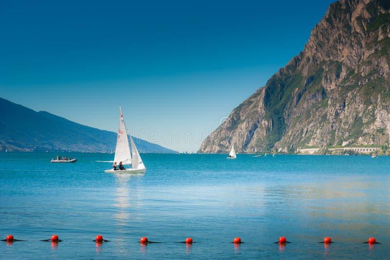 因为背景是蓝色的小船小船可能棍打浮动旅馆图象略写法海洋红色风船航行风帆被传统化的使用的通知游艇黄色的黑暗的等标志 免版税库存图片