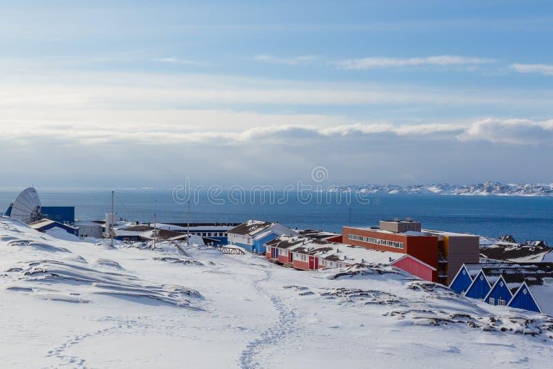因纽特人在雪盖的村庄房子在努克市,格陵兰海湾  图库摄影
