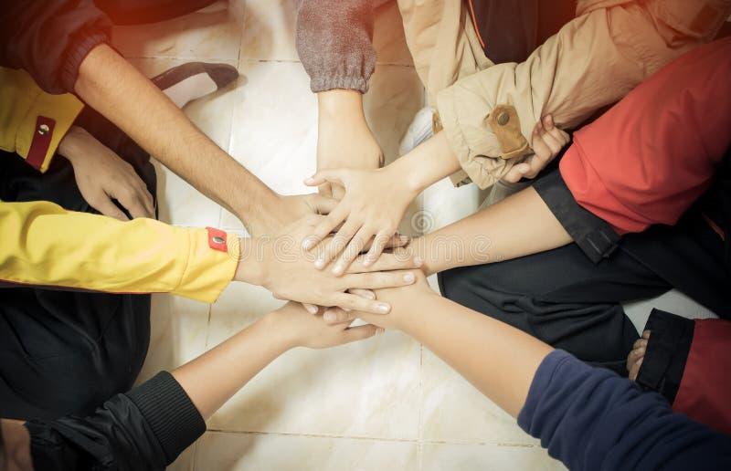 团结和配合概念:小组一起朋友手 汇集他们的手的亚裔年轻人顶视图作为朋友 库存照片