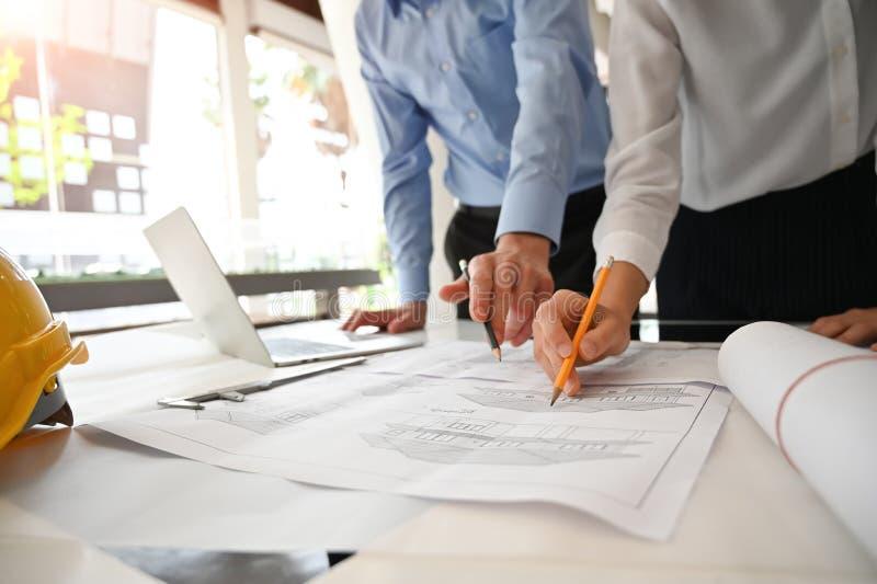 团队架构师在建筑办公室与蓝图和计算机会面和咨询 免版税库存照片