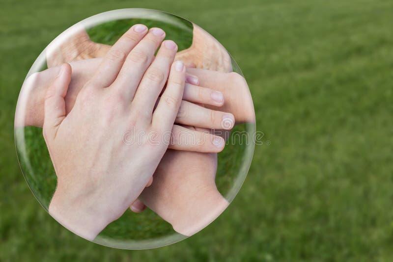 团结在草的玻璃球形的手 库存图片