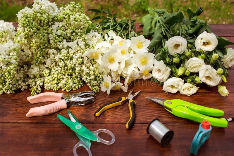 园艺工具、工具为floristics和花在一张木桌上 免版税库存照片