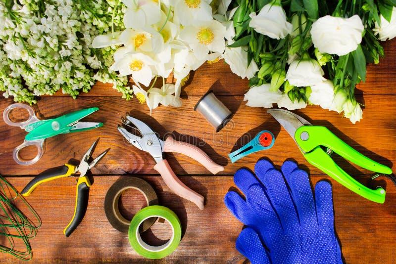 园艺工具、工具为floristics和花在一张木桌上 库存图片