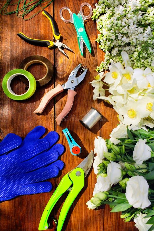 园艺工具、工具为floristics和花在一张木桌上 免版税库存图片