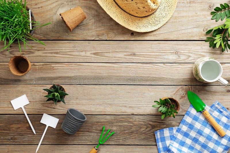 园艺工具、花在罐,草和草帽在葡萄酒木背景 春天庭院运作概念 平的位置 免版税库存照片