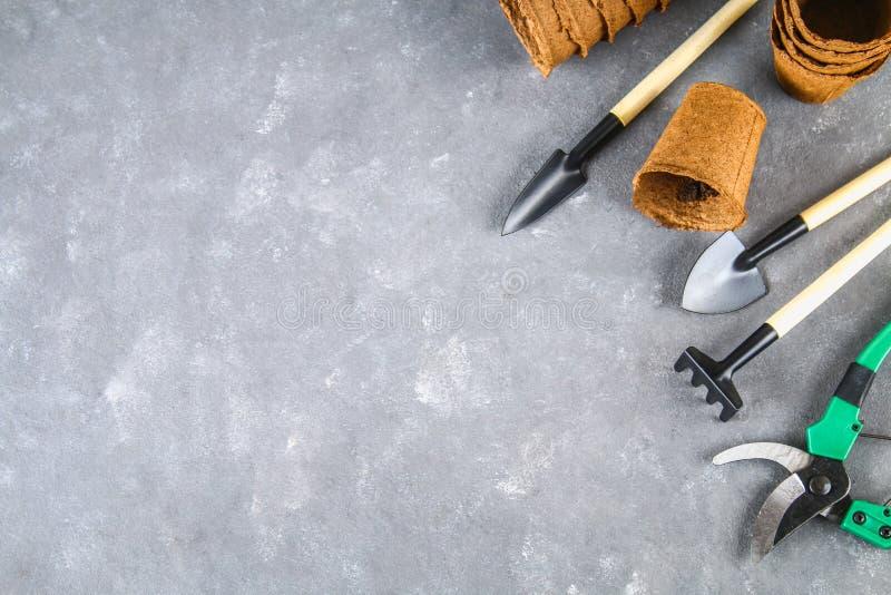 园艺工具和罐在灰色具体背景 顶视图,拷贝空间 免版税库存图片