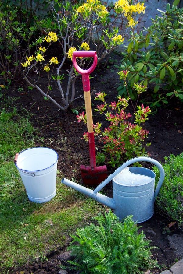 园艺工具铁锹锹老锌喷壶桶袋子在有花和草的庭院里 图库摄影