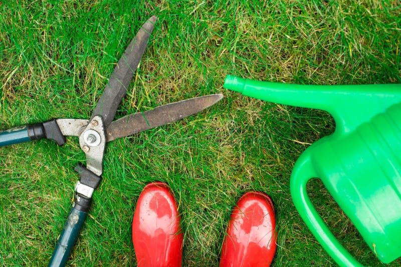 园艺工具,红色庭院鞋子,剪枝夹,在草的喷壶,关闭  免版税库存照片