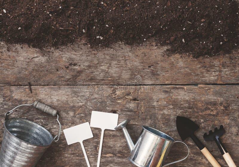 园艺工具,铁锹,犁耙,一把喷壶,桶,桌 免版税库存照片