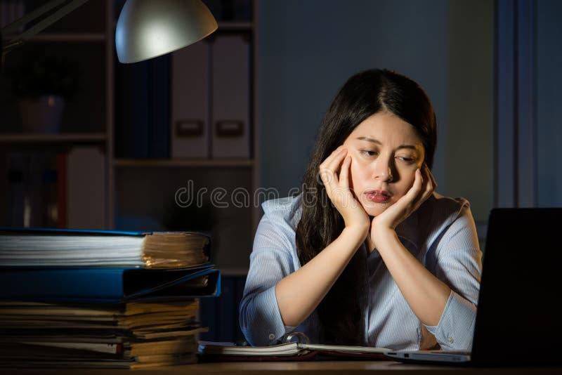 困亚裔的女商人工作超时夜间 免版税库存照片