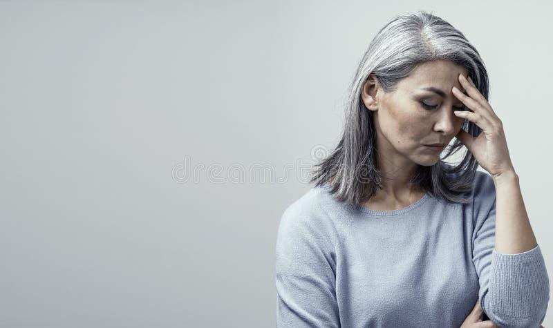 困厄的亚裔妇女在白色背景 免版税库存照片