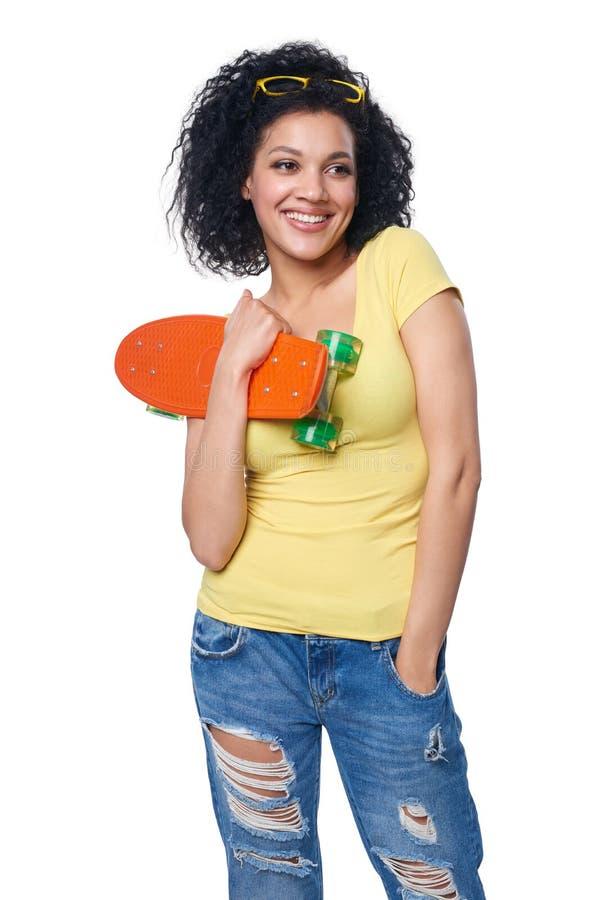 困厄的牛仔裤的愉快的微笑的混合的族种女性有滑板的 库存图片