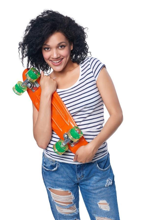困厄的牛仔裤的愉快的微笑的混合的族种女性有滑板的 免版税库存图片