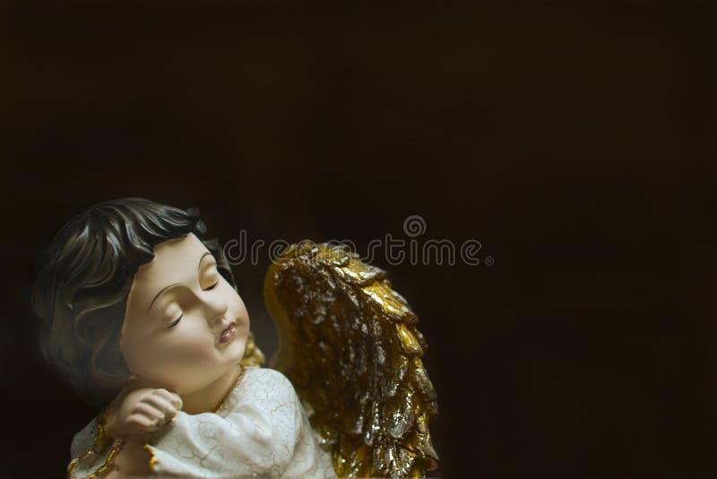 困天使木小雕象与黑发的 库存图片