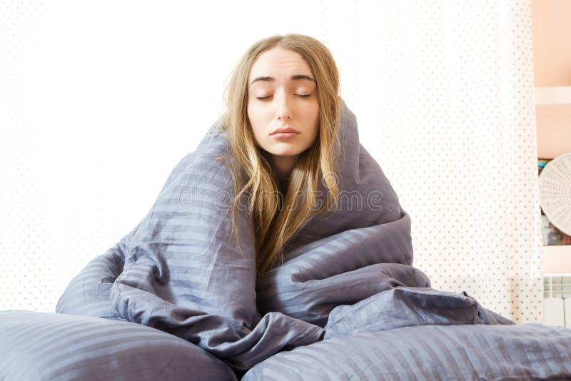 困女孩早晨在床上,在毯子包裹的年轻美女睡觉 基于卧室的困秀丽妇女 免版税库存照片