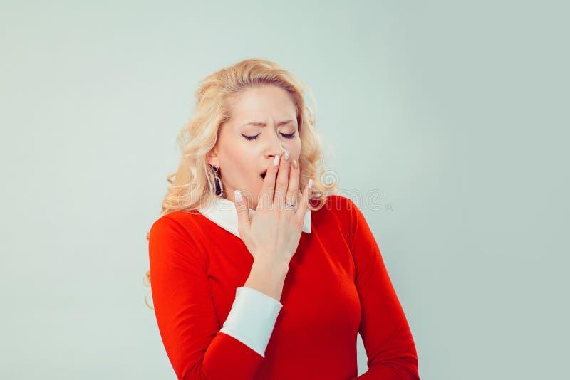困妇女覆盖物嘴,当打呵欠时 免版税图库摄影