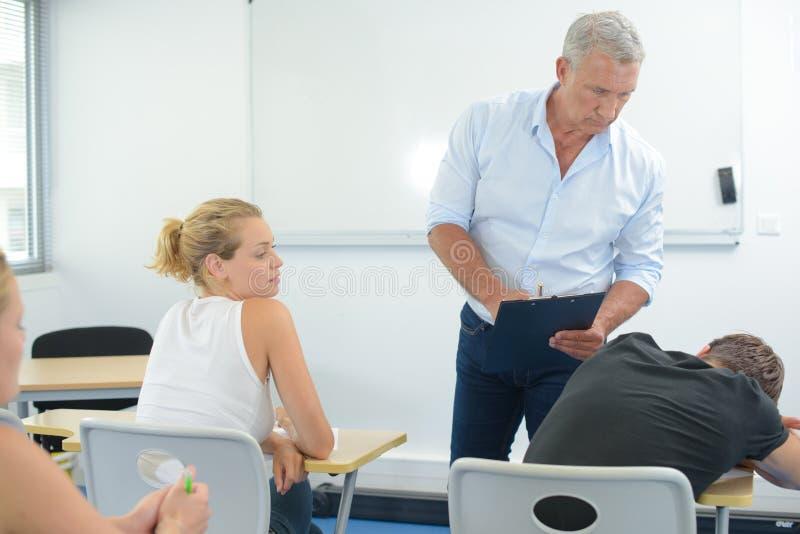 困学生和不快乐的老师在教室 免版税库存图片