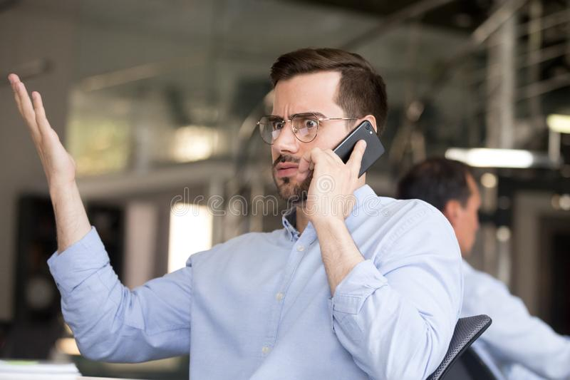 困惑的商人谈话在电话在办公室 免版税库存照片