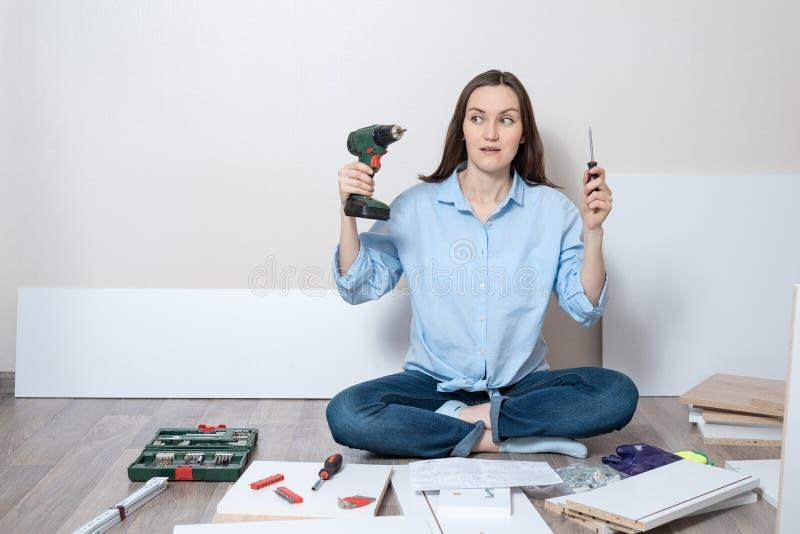 困惑的妇女在手中坐与螺丝刀和电螺丝刀的地板,家具汇编 库存图片