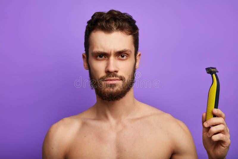 困惑的帅哥看窘迫电动剃须刀 图库摄影