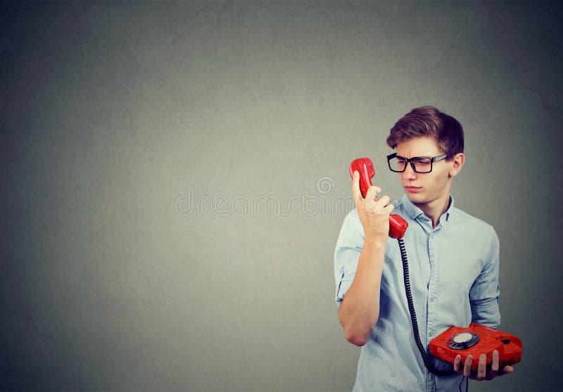 困惑的年轻人说在电话里 库存图片