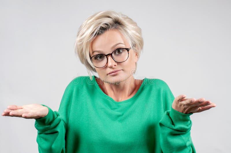 困惑的犹豫的妇女耸表达的肩不确定性 免版税库存图片