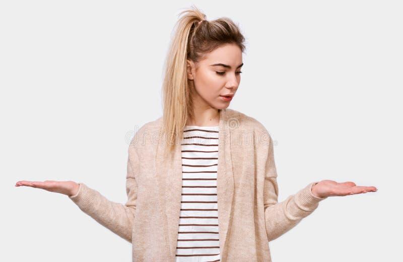 困惑的白肤金发的俏丽的年轻女人耸肩肩膀画象,看起来不定,迷茫,并且看对手棕榈,有疑义 免版税库存图片