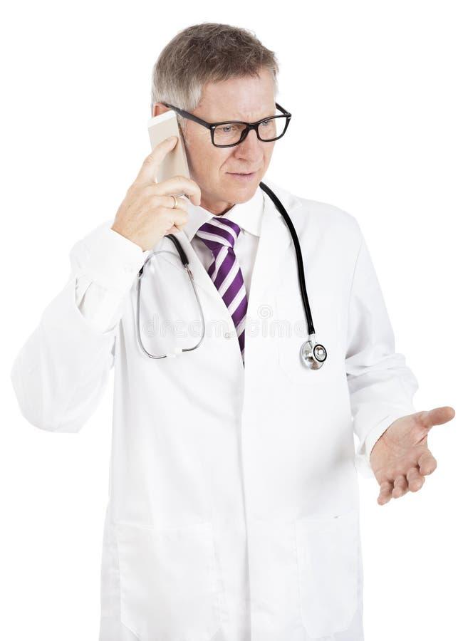 困惑的医生谈话在他的手机 免版税库存照片