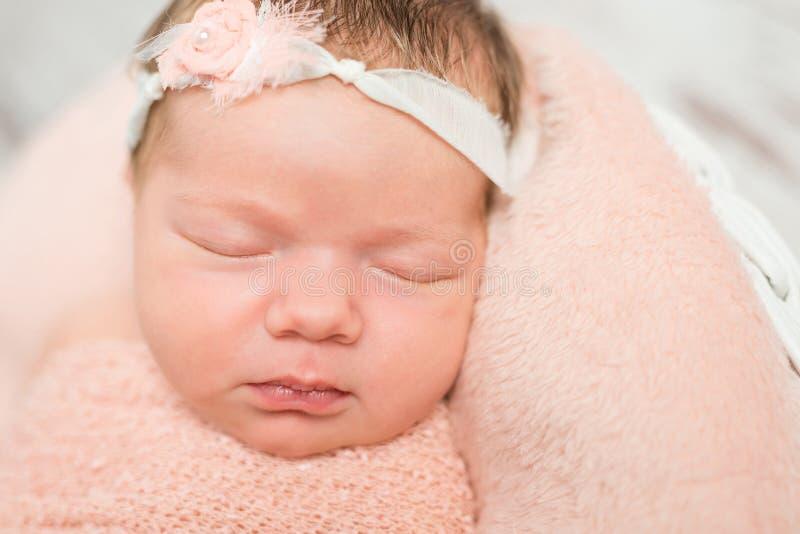 困新出生的婴孩的逗人喜爱的面孔有发带的 库存照片