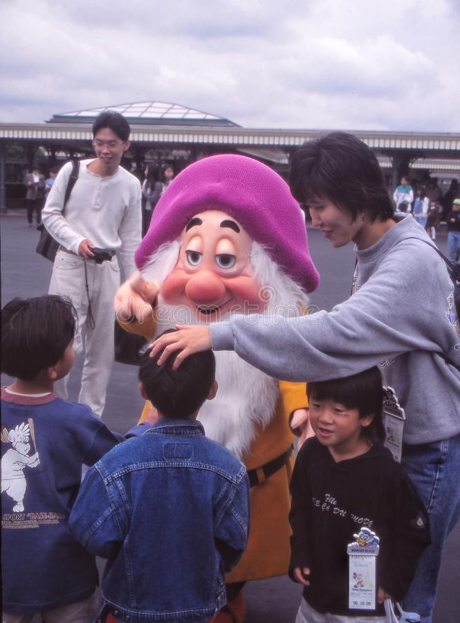 困矮人在东京迪斯尼乐园招呼家庭 库存照片
