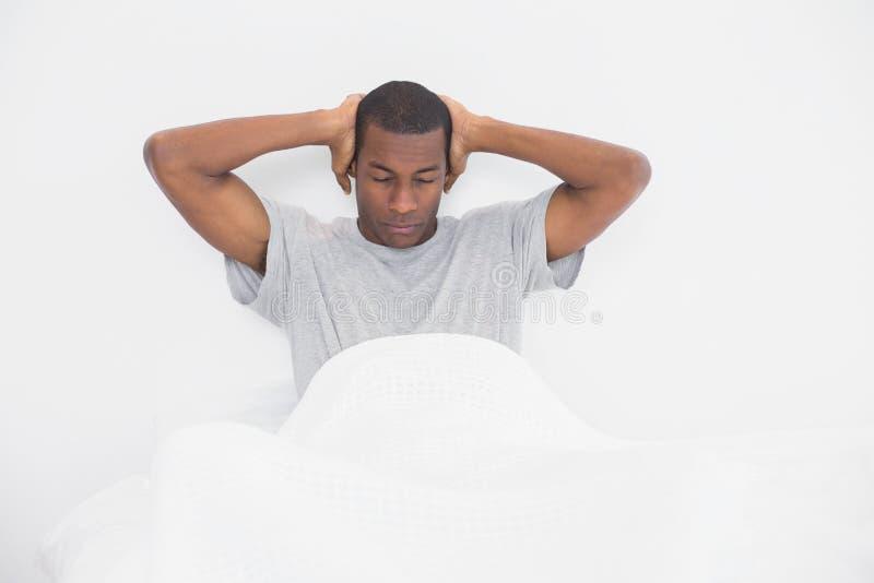困蓬松卷发人覆盖物耳朵用手在床上 库存照片